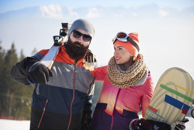 Paret med snowboards och skidar arkivbilder