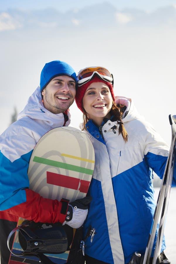 Paret med snowboards och skidar arkivfoto