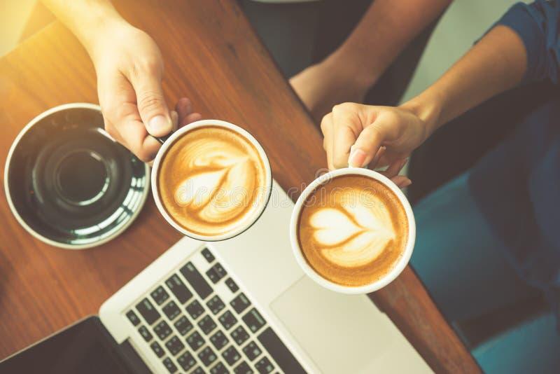 Paret räcker den hållande kaffekoppen på det funktionsdugliga skrivbordet med bärbara datorn royaltyfri bild