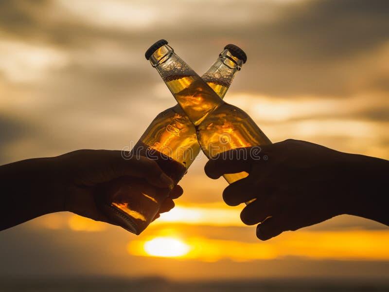 Paret räcker hållande ölflaskor och att klinga på solnedgångbeaen royaltyfri fotografi