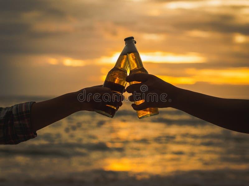 Paret räcker hållande ölflaskor och att klinga på solnedgångbeaen arkivbilder