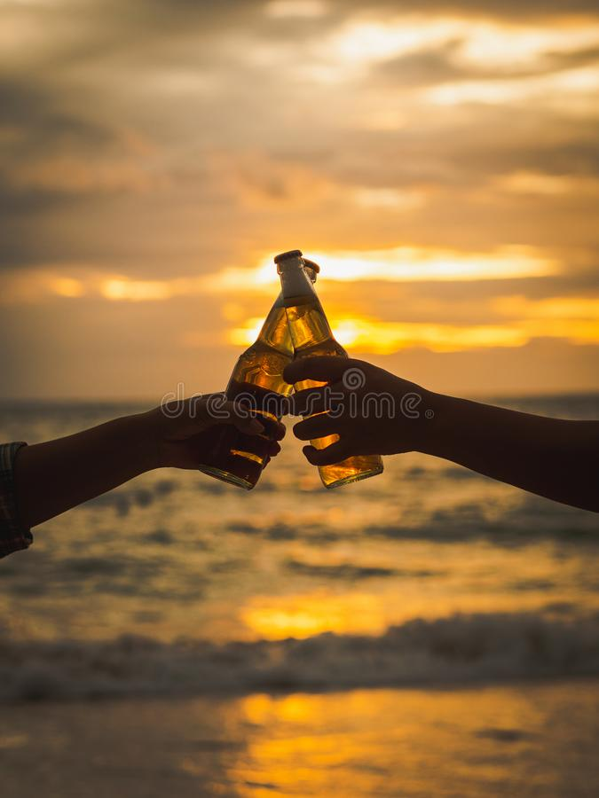 Paret räcker hållande ölflaskor och att klinga på solnedgångbeaen fotografering för bildbyråer