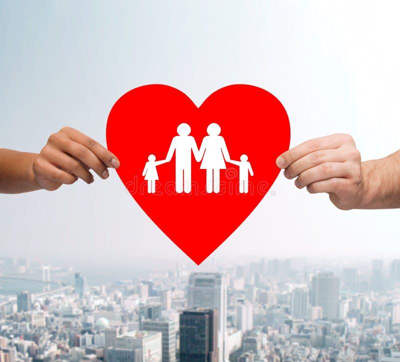 Paret räcker hållande röd hjärta med familjen arkivbild