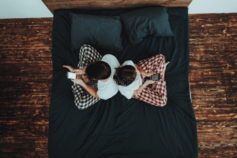 Paret sitter på säng och använder mobiltelefoner arkivbild