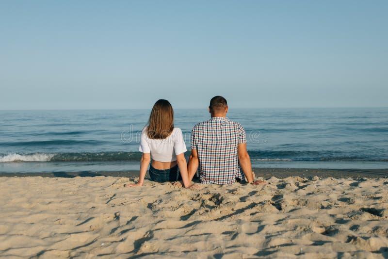 Paret sitter på stranden, den bakre sikten royaltyfri foto