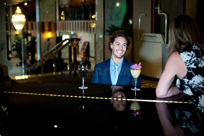 Paret som tycker om rogivande musik som grabb, planerar pianot royaltyfri foto