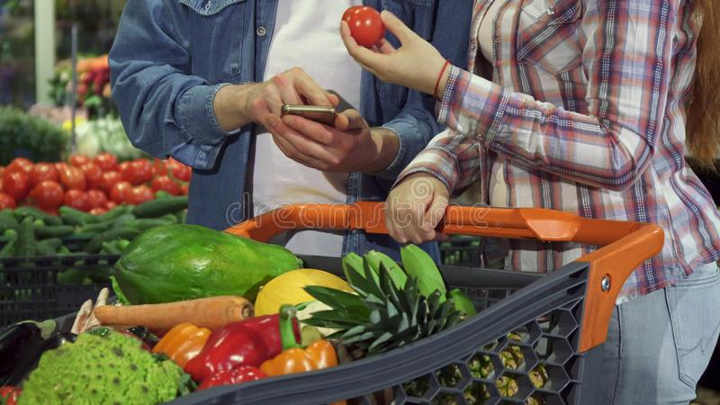Paret sorterar ut grönsaker och frukter i livsmedelsbutikvagn royaltyfri bild