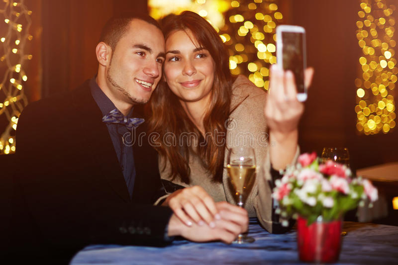 Paret spenderar valentins dag i restaurangen och som fotograferar i minne arkivfoton