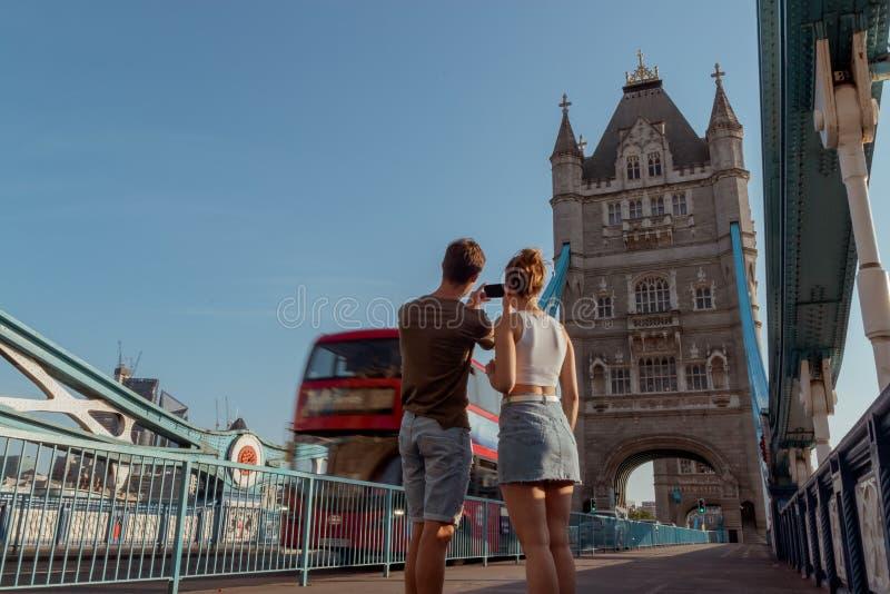 Paret tar en bild av en röd buss för dubbel däckare på tornbron i London fotografering för bildbyråer
