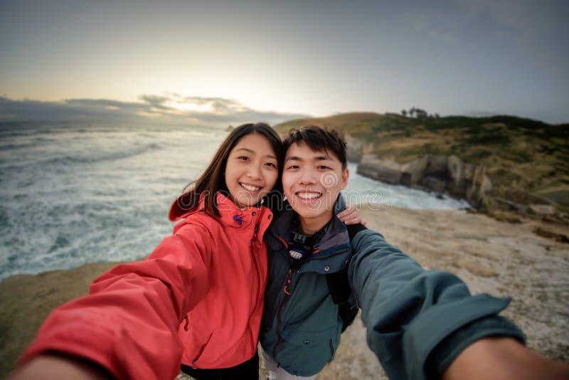 Paret tar selfiebild på kust- landskap nära Dunedin i Nya Zeeland arkivfoton