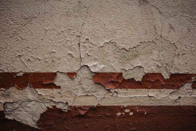 parete bianca, dettaglio di una banda rossa abbandonata e di sbriciolatura della parete immagini stock