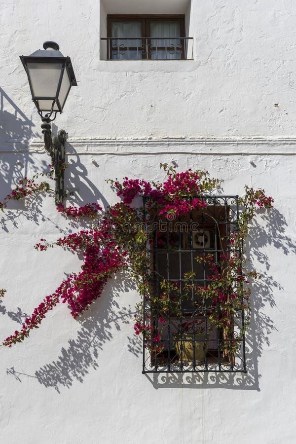 Parete bianca di una casa con una finestra e una lampada di via in una vecchia città provinciale immagine stock