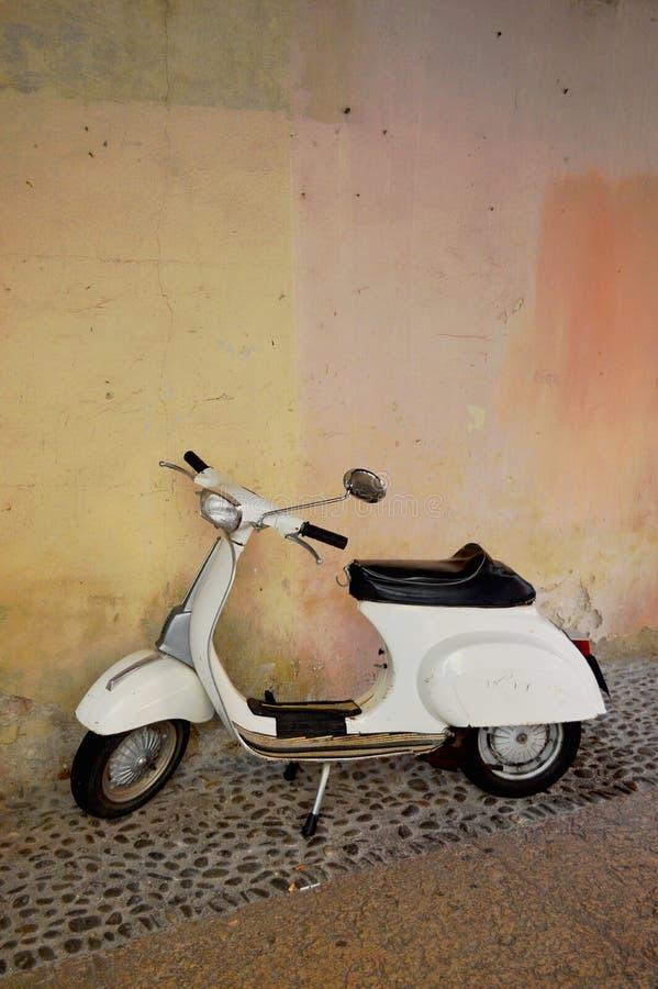 Parete colorata pastello del gesso nel fondo con il motorino italiano bianco immagini stock libere da diritti