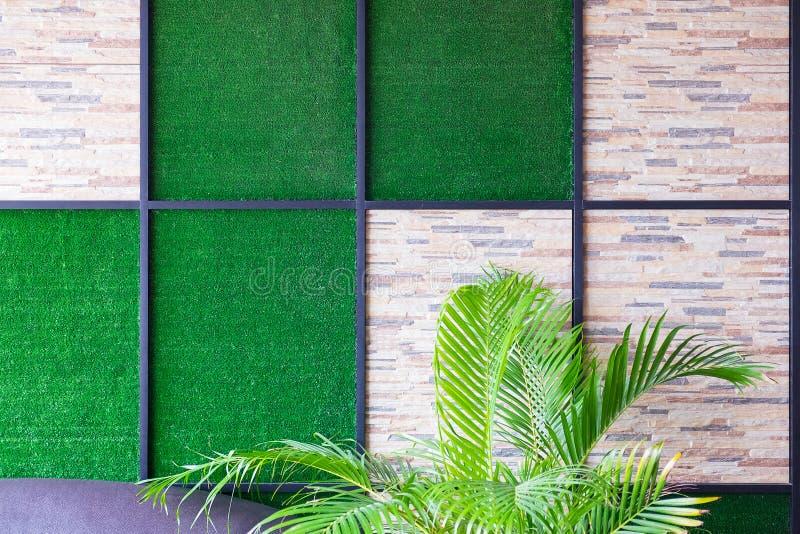 Parete del fondo di pietra ed artificiale dell'erba con la struttura a del metallo fotografie stock