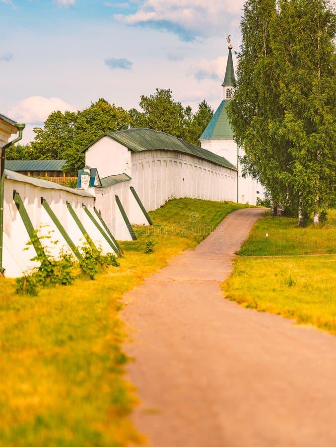 Parete del monastero con la strada in prato ed in alberi fotografia stock