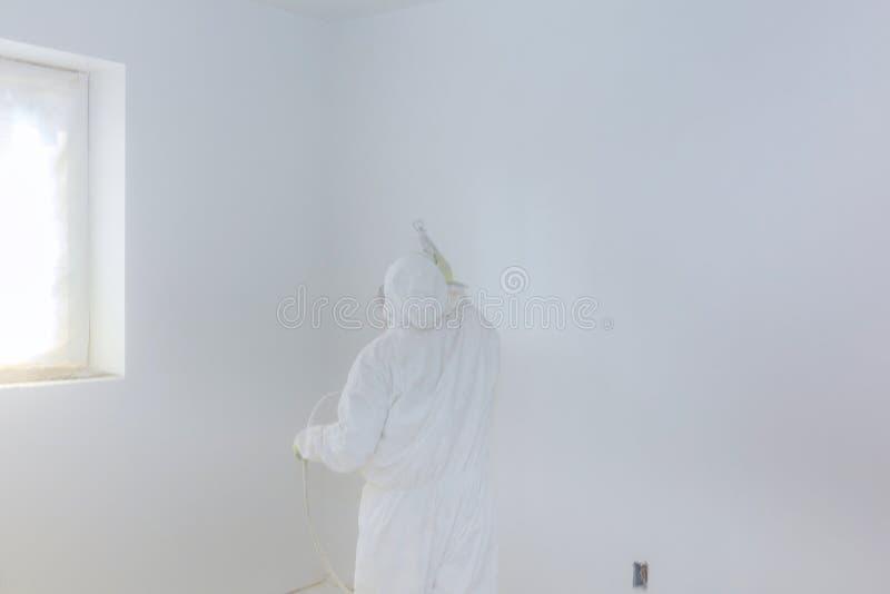 Parete della pittura del lavoratore con la pistola a spruzzo nel colore bianco fotografie stock