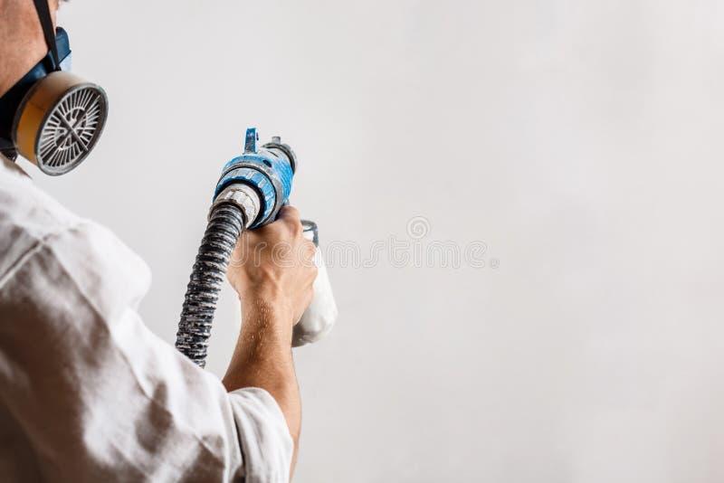Parete della pittura del lavoratore con la pistola a spruzzo nel colore bianco fotografia stock