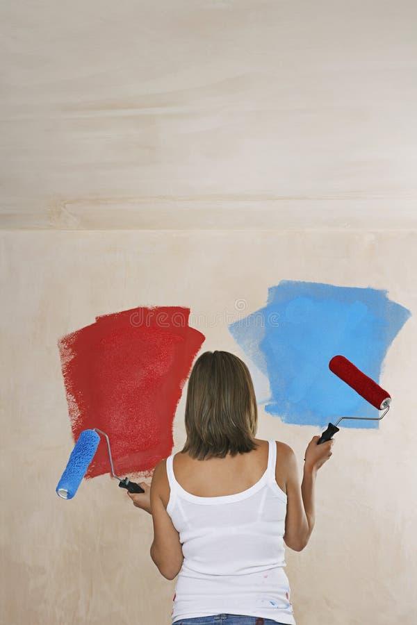 Parete della pittura della donna rossa e blu con i rulli di pittura fotografia stock libera da diritti