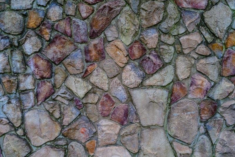 Parete delle pietre colorate fissate con cemento, fondo fotografie stock libere da diritti
