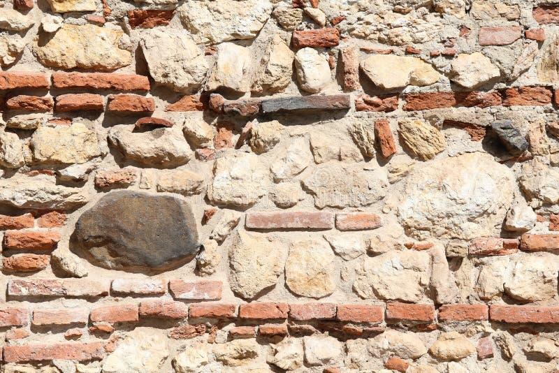 Parete delle pietre e dei mattoni rossi con calce e cemento fotografie stock