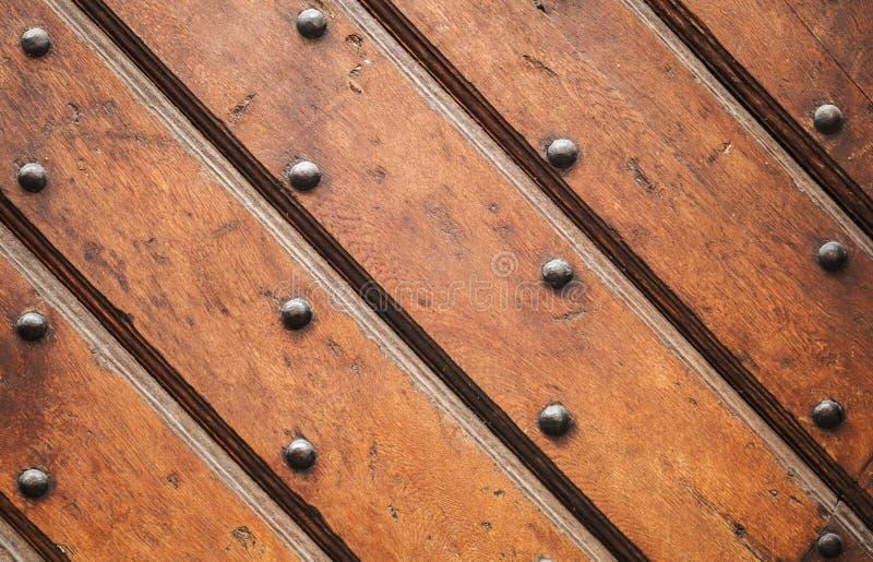 Parete di legno marrone d'annata con i chiodi decorativi fotografie stock