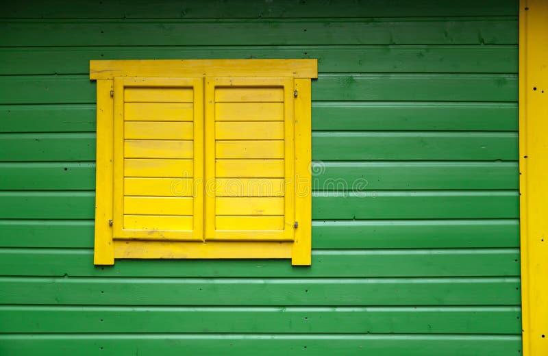 Parete di legno verde con la finestra gialla fotografie stock
