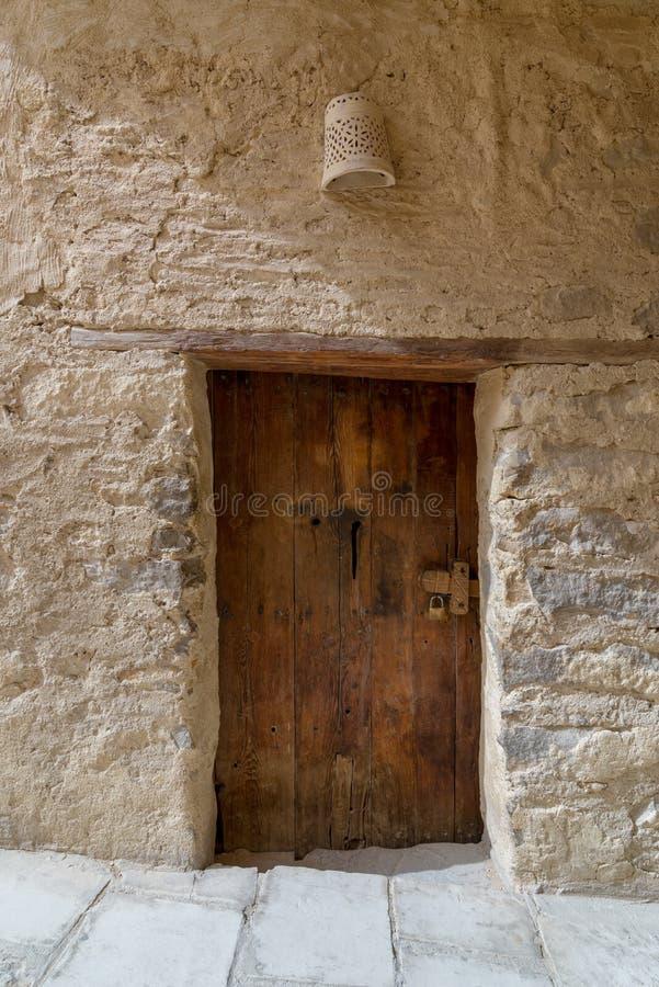 Parete di mattoni di pietra antica e vecchia porta di legno immagine stock libera da diritti