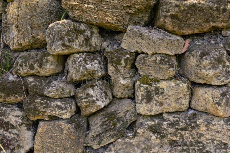 Parete di pietra antica coperta di muschio una pietra naturale Fondo creativo d'annata fotografia stock libera da diritti
