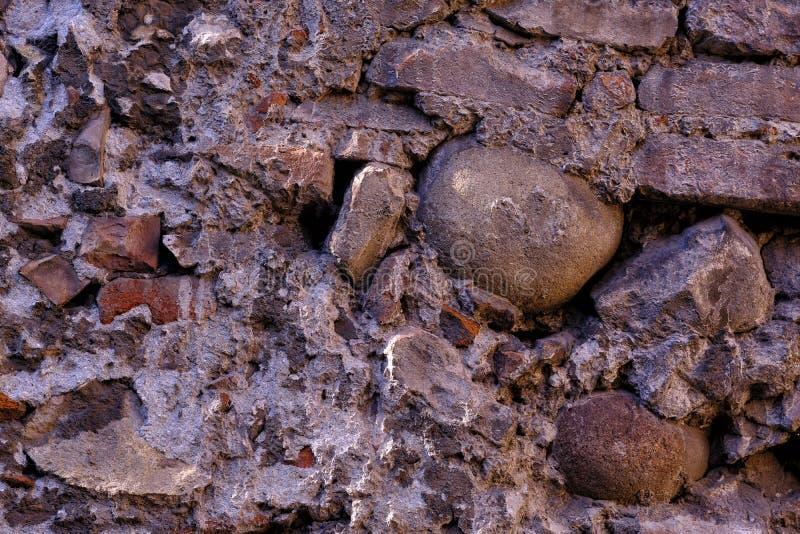 Parete di pietra antica, vecchia argilla e massi fotografia stock