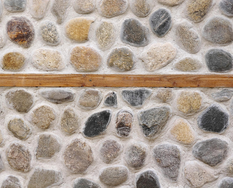 Parete di pietra con il primo piano del fascio di legno fotografia stock libera da diritti