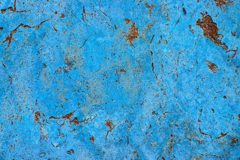 Parete di pietra della ciano facciata blu di colore con le imperfezioni, i fori di rosso arancio e le crepe come fondo rustico e  fotografie stock libere da diritti