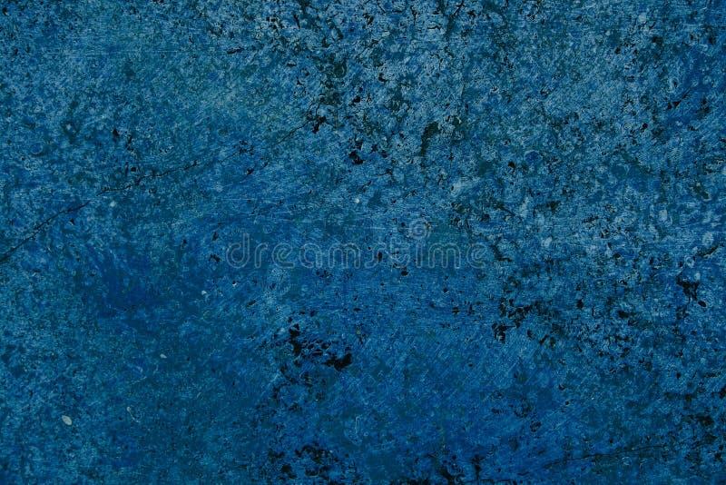 Parete di pietra della facciata blu luminosa viva di colore con le imperfezioni e crepe come struttura rustica e semplice vuota d immagine stock