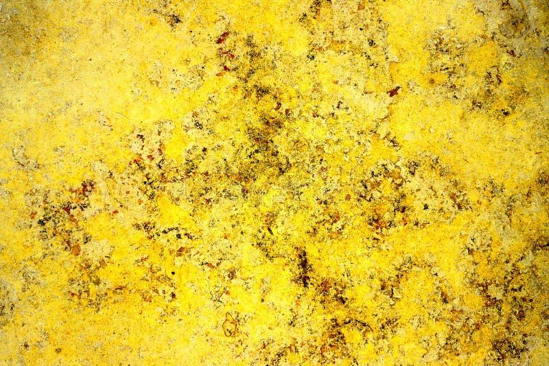 Parete di pietra della facciata gialla dorata di colore con le imperfezioni, i fori e le crepe come struttura astratta rustica e  immagini stock libere da diritti
