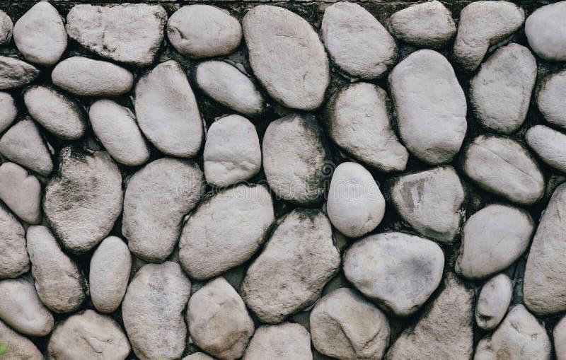 Parete di pietra grigia o grigia con la pietra rotonda di struttura naturale Parete di pietra naturale di vecchio stile fotografia stock libera da diritti