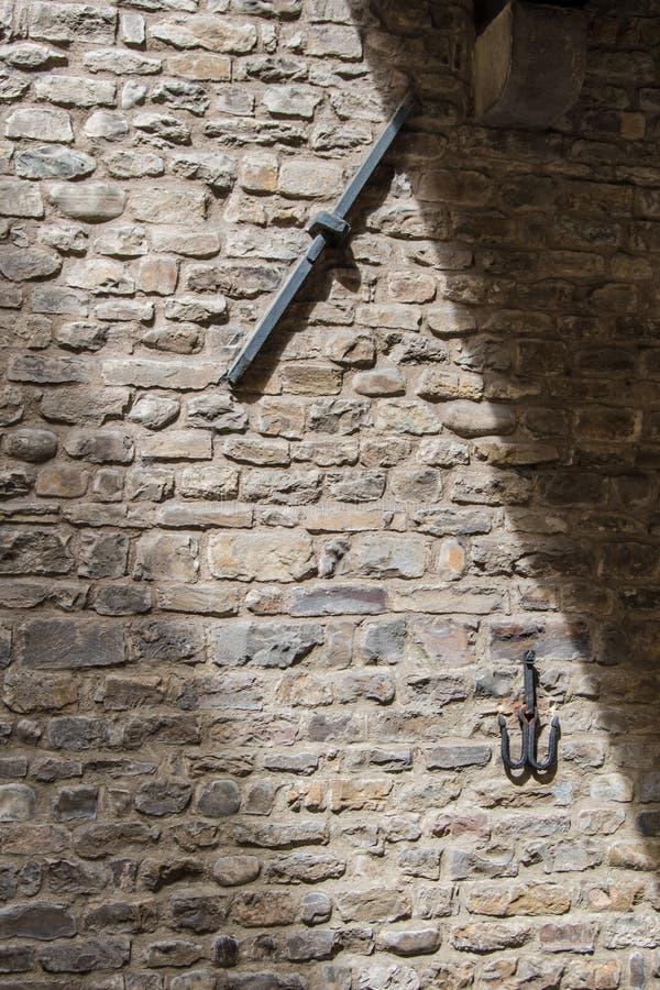 Parete di pietra medievale antica con le inserzioni del ferro nel centro della F fotografia stock