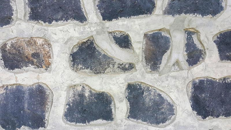 Parete di pietra nera, recinto di struttura, pietre poste e riparate con la linea grigia spessa concreta modellata concreta e vis fotografia stock libera da diritti
