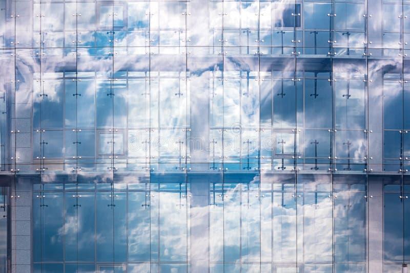 Parete di vetro blu dell'edificio per uffici con la riflessione delle nuvole e del cielo fotografia stock libera da diritti