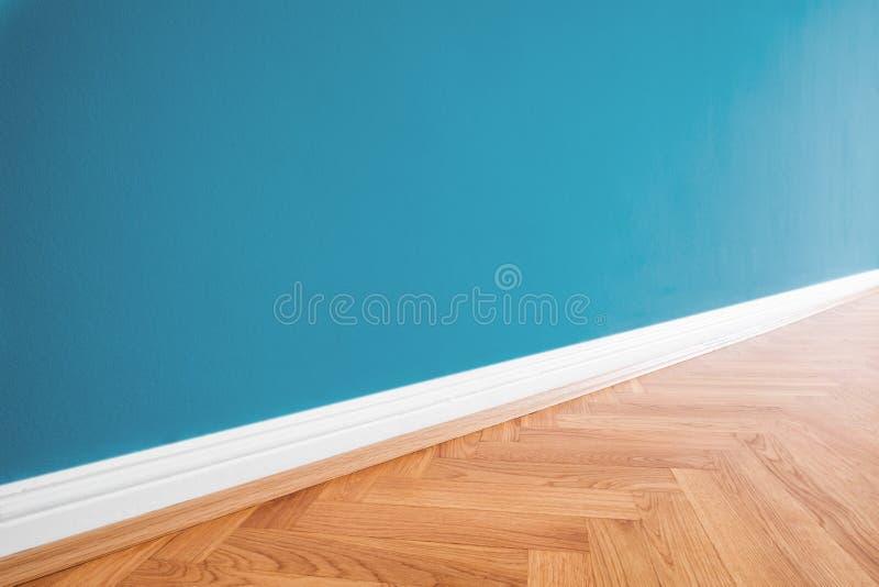 Parete dipinta blu e pavimento di parquet di legno - fondo di rinnovamento immagine stock