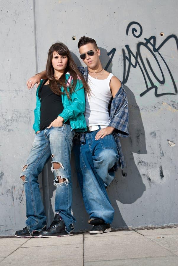 Parete diritta del ritratto di giovane modo urbano delle coppie fotografia stock