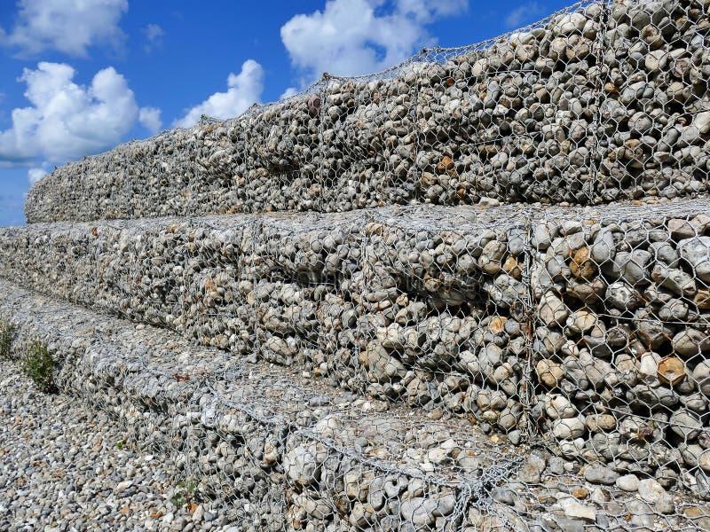 Parete fatta delle rocce rotonde, fissato con la rete del filo di acciaio, gabbione di pietra del ferro fotografia stock libera da diritti