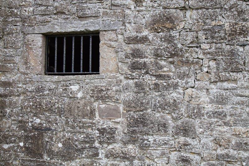 Parete medievale della prigione con una finestra immagini stock libere da diritti