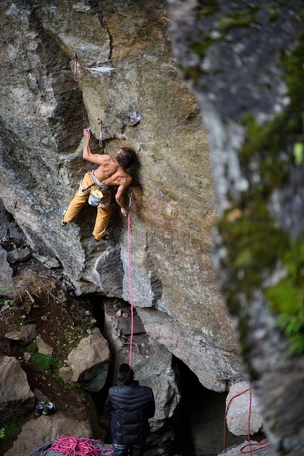 Parete rampicante della scogliera del giovane scalatore maschio atletico Copi lo spazio a destra fotografie stock