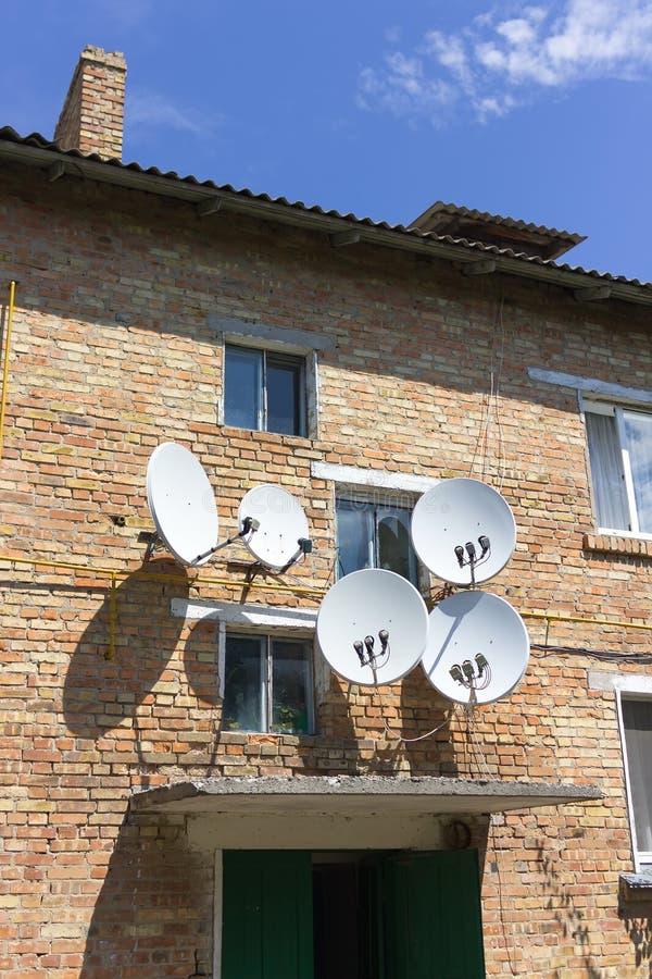 Parete rossa della casa con mattoni a vista con le antenne del piatto del riflettore parabolico immagine stock libera da diritti