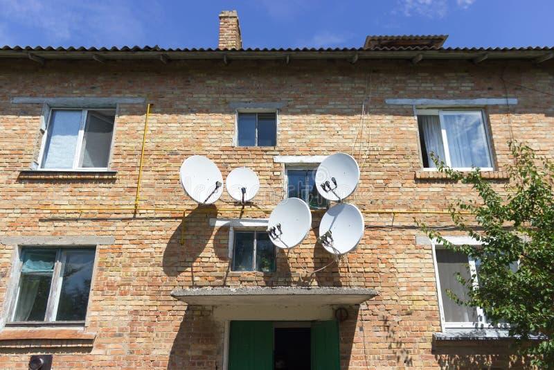 Parete rossa della casa con mattoni a vista con le antenne del piatto del riflettore parabolico fotografie stock