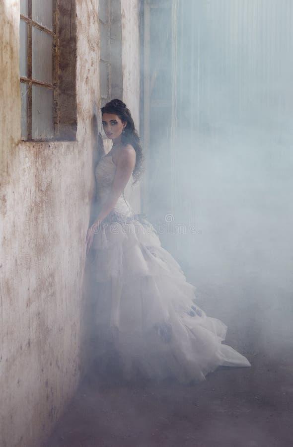 Parete rustica pendente del agaisnt della sposa sexy di fantasia circondata da nebbia immagini stock