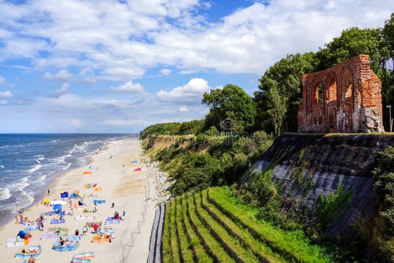 A parete semplice della chiesa rovinata sull'orlo della scogliera, la gente sulla spiaggia sabbiosa qui sotto fotografie stock