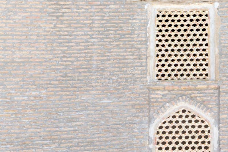 Parete storica antica centroasiatica del ` s della costruzione Un vecchio muro di mattoni del Medio-Oriente di due finestre fotografia stock