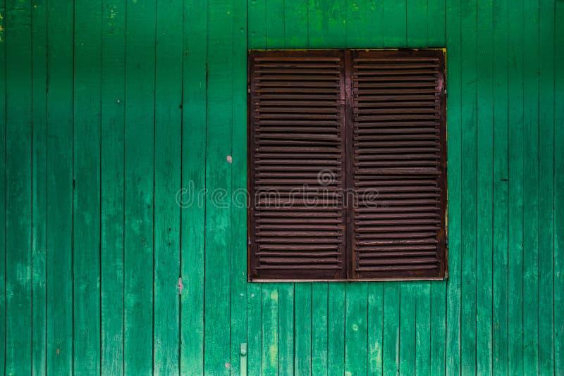 Parete verde e di legno con la finestra chiusa fotografia stock
