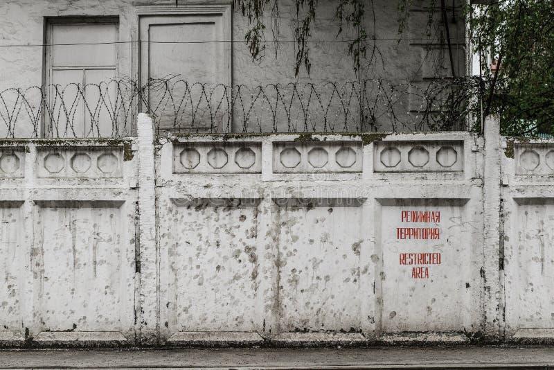 Pareti divisorie con filo spinato e l'area di Restrikted dell'iscrizione fotografie stock