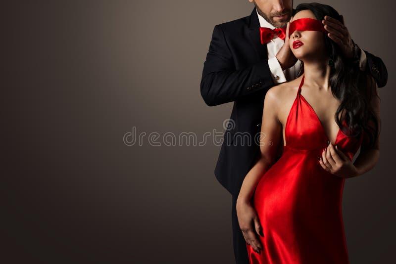 Parförälskelsekyss, man och sexig bunden för ögonen på kvinna i röd klänning arkivfoto